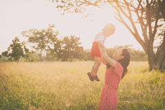 Happy family. A mother and son playing in grass fields outdoors Royalty Free Stock Photos