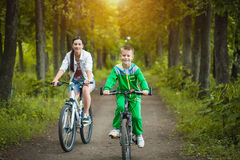 Happy family. mother and son riding  in the park Royalty Free Stock Image