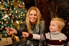 Happy family mother and son with sparkler near a Christmas tree royalty free stock image