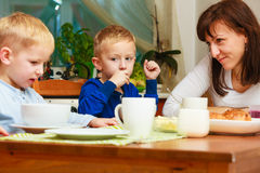 Happy family. Mother and sons eating breakfast. stock photography