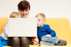 Happy family. Mother and sons using laptop sitting on sofa at home. Happy family. Mother young women and boys kids children sons using laptop computer sitting on Stock Photo