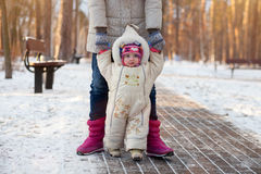 A happy family. Mother teaches a child to walk in winter park. Stock Image