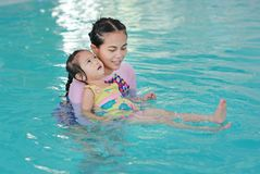 Family of mother teaching kid in swimming pool stock photography