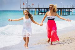 Happy family mother and teenager daughter run, laugh and play at beach stock images