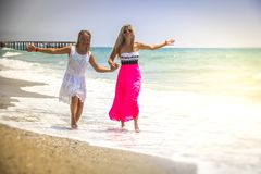 Happy family mother and teenager daughter run, laugh and play at beach royalty free stock images