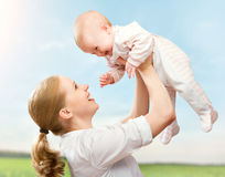 Happy family. Mother throws up baby in the sky. Happy family. Mother throws up  baby in the sky in nature Stock Photos