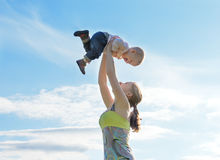Happy family. Mother throws up baby in the sky Royalty Free Stock Images