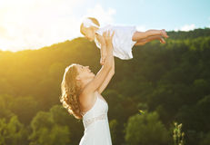 Happy family. Mother throws up baby in the sky Stock Photo
