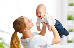 Happy family mother  throws up child baby at home Royalty Free Stock Image