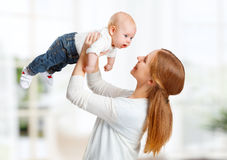 Happy family mother  throws up child baby at home Royalty Free Stock Images