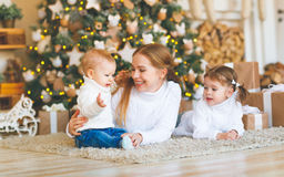 Happy family mother and two children on Christmas morning  tree. Happy family mother and two children  on Christmas morning at the Christmas tree with gifts Royalty Free Stock Photography