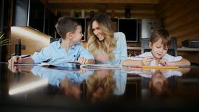 Happy family mother of two children helps the sons to do their homework sitting at the big table in the kitchen. Happy family mother of two children helps the stock video footage