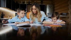 Happy family mother of two children helps the sons to do their homework sitting at the big table in the kitchen. Happy family mother of two children helps the stock footage