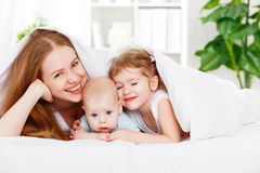 Happy family mother and two children, son and daughter in bed un. Happy family mother and two children, son and daughter in bed playing under blanket stock photography