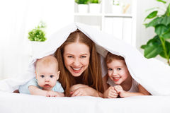Happy family mother and two children, son and daughter in bed un Stock Photography
