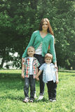 Happy family! Mother with two children sons walks on nature. Together hugging standing on the grass in summer day royalty free stock photography