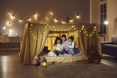 Free Happy Family Mother With Daughters Kid Reading Book Sitting In Tent At Home Stock Image - 212548311