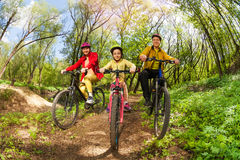Happy family mountain biking on forest trail Royalty Free Stock Image