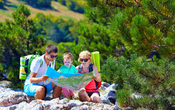 Happy family in mountains discussing the route Stock Photo