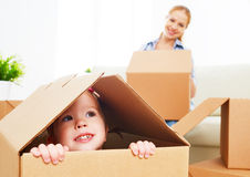 Happy family moves into a new apartment. happy baby in a cardboa Stock Photos