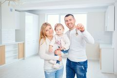 A happy family moves to a new apartment. Mother, father and child with boxes in the room of the new house Royalty Free Stock Photo
