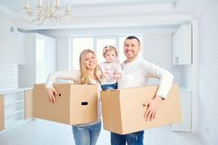 A happy family moves to a new apartment. Mother, father and child with boxes in the room of the new house Stock Photo