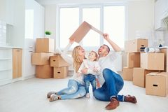 A happy family moves to a new apartment. Mother, father and child with boxes in the room of the new house Stock Image