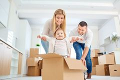 A happy family moves to a new apartment. Mother, father and child with boxes in the room of the new house Stock Photos