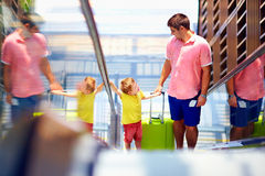 Happy family moving on escalator, with boarding pass in hands Royalty Free Stock Photography