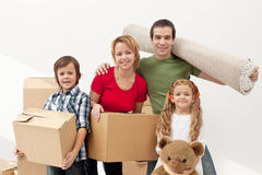 Happy family moving into a new home. Carrying their stuff Royalty Free Stock Images