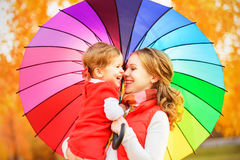 Happy family mum and child daughter with rainbow colored umbrell Stock Photo