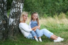 Happy family in nature. Beautiful and happy mother gently hugs her little daughter with blond hair against the background of grass Stock Image