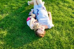 Happy family on nature. Mom and toddler baby daughter laying and relaxing, hugging, on green grass meadow at evening sunset. Spend stock photos