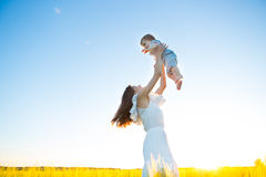 Happy family on nature outdoors mother and baby son. On the green meadow stock photography