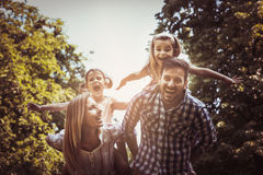 Happy family in nature. Parents carrying their daughter on piggyback Royalty Free Stock Image