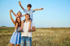 Happy family in nature smiling with their hands up. Stock Image