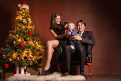 Happy family near Christmas tree at home. Closeup portrait of cute cheerful family near Christmas tree at home, happy parents with baby celebrate New Year Royalty Free Stock Image