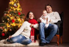Happy family near Christmas tree at home. Closeup portrait of cute cheerful family near Christmas tree at home, happy parents with baby celebrate New Year Royalty Free Stock Photos