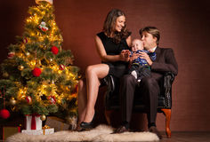 Happy family near Christmas tree at home. Closeup portrait of cute cheerful family near Christmas tree at home, happy parents with baby celebrate New Year Stock Image