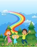 A happy family near the pine trees with a rainbow in the sky Royalty Free Stock Images