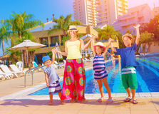 Happy family near pool. Happy family having fun near pool on luxury beach resort, sunny day, all together raised up hands, enjoying summer holidays, happiness Royalty Free Stock Photo