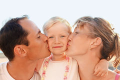 Happy family near to sea, parents kiss daughter