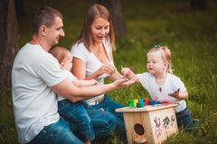 Happy family with nesting box and paints Royalty Free Stock Photos