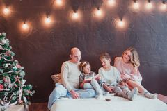 Happy family in the new year`s interior sitting on the bed and reading a book. They`re smiling. Next is a Christmas tree royalty free stock images