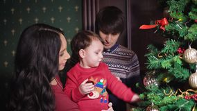 A happy family at a New Year tree. The kid on hands at the smiling mother is played by a Christmas tree decoration. The. Man corrects a fir-tree. Parents watch stock video
