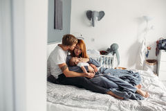 Happy family with newborn baby on the bed Stock Photos