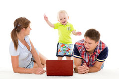 Happy family with notebook. Stock Photos