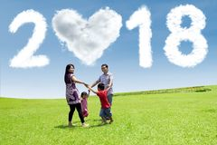 Happy family with numbers 2018 in the park. Happy family playing together in the park with clouds shaped numbers 2018 and heart in the sky Royalty Free Stock Image