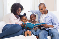 Happy Family On The Couch Reading Storybook Royalty Free Stock Image