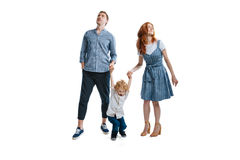Happy family with one child holding hands and looking away Stock Image